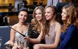 Femmes avec le smartphone prenant le selfie à la boîte de nuit Image libre de droits