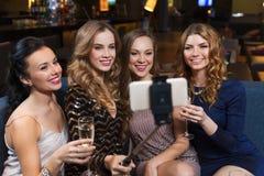 Femmes avec le smartphone prenant le selfie à la boîte de nuit Photos stock
