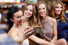 Femmes avec le smartphone prenant le selfie à la boîte de nuit Image stock