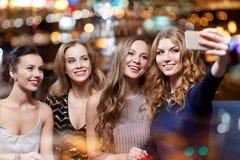 Femmes avec le smartphone prenant le selfie à la boîte de nuit Photo libre de droits