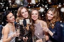 Femmes avec le smartphone prenant le selfie à la boîte de nuit Photo stock