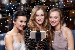 Femmes avec le smartphone prenant le selfie à la boîte de nuit Photographie stock libre de droits
