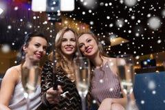 Femmes avec le smartphone prenant le selfie à la boîte de nuit Images stock