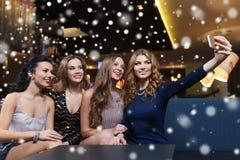 Femmes avec le smartphone prenant le selfie à la boîte de nuit Photographie stock