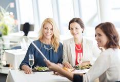 Femmes avec le smartphone prenant le selfie au restaurant Images libres de droits