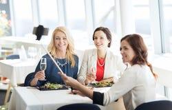 Femmes avec le smartphone prenant le selfie au restaurant Image libre de droits