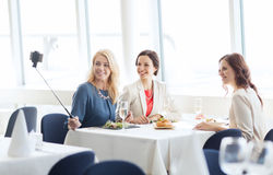 Femmes avec le smartphone prenant le selfie au restaurant Photo stock