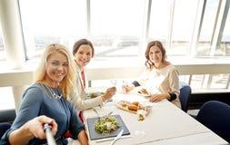 Femmes avec le smartphone prenant le selfie au restaurant Photographie stock libre de droits