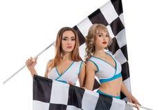 Femmes avec les drapeaux à carreaux de course d'isolement sur le blanc Photos stock