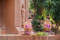 Femmes avec les robes traditionnelles pliant le pétale de lotus Image stock