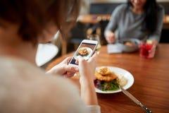 Femmes avec les smartphones et la nourriture au restaurant Images stock