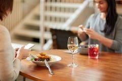 Femmes avec les smartphones et la nourriture au restaurant Photos stock