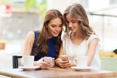 Femmes avec les smartphones et le café au café extérieur Photographie stock libre de droits