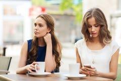 Femmes avec les smartphones et le café au café extérieur Images libres de droits