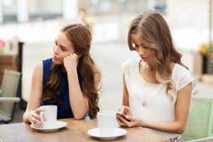 Femmes avec les smartphones et le café au café extérieur Photos libres de droits