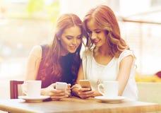 Femmes avec les smartphones et le café au café extérieur Photos stock