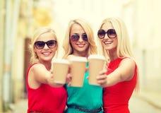 Femmes avec les tasses de café à emporter dans la ville Image libre de droits