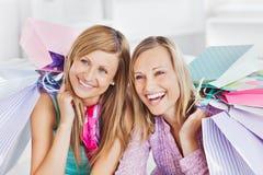 Femmes avec plaisir retenant des sacs à provisions et le sourire Photo libre de droits