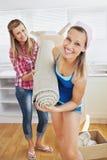 Femmes avec plaisir retenant un tapis dans leur maison Image libre de droits