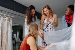 Femmes ayant l'amusement pendant la sélection de robe de mariée dans la boutique images stock