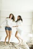 Femmes ayant l'amusement sur le lit Photographie stock