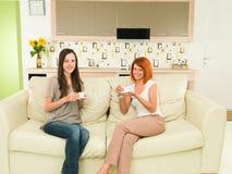Femmes ayant l'amusement tout en buvant du café Images stock