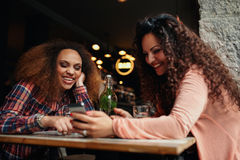 Femmes ayant l'amusement utilisant un téléphone intelligent en café Image libre de droits