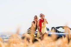 Femmes ayant la balade en voiture dans la voiture convertible ayant le repos Photographie stock libre de droits