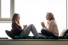 Femmes ayant le thé à la maison sur le lit de rebord de fenêtre Image stock