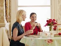 Femmes ayant le thé à la table de salle à manger Photographie stock libre de droits