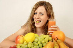 Femmes blondes avec les fruits frais et le jus d'orange Image libre de droits