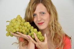Femmes blondes avec un groupe de raisins Image stock