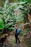 Femmes blondes de Yong avec l'appareil-photo et le sac à dos bleu marchant par la plantation de banane sur l'itinéraire de trekki Images libres de droits