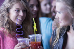 Femmes buvant des cocktails à la boîte de nuit Photographie stock libre de droits