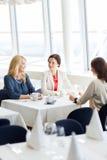 Femmes buvant du café et parlant au restaurant Image stock