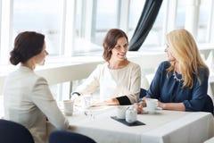 Femmes buvant du café et parlant au restaurant Photos stock