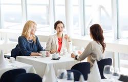 Femmes buvant du café et parlant au restaurant Photographie stock