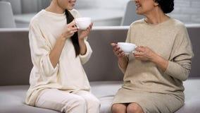 Femmes buvant du thé et communiquant, mère de visite de fille, agrément à la maison photos libres de droits