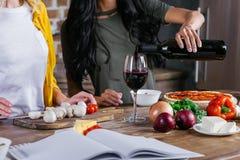 Femmes buvant du vin tout en faisant cuire la pizza ensemble Image stock
