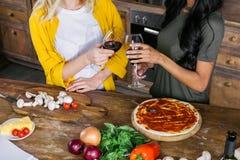 Femmes buvant du vin tout en faisant cuire la pizza ensemble Images stock