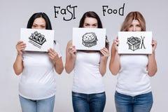 Femmes calmes se tenant et protestant contre manger des aliments de préparation rapide malsains Photographie stock libre de droits