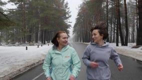 Femmes caucasiennes sup?rieures et jeunes heureuses courant en parc neigeux en hiver parlant et souriant ?troitement d'avance sui banque de vidéos