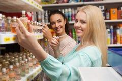 Femmes choisissant le parfum dans le magasin de beauté Photos libres de droits
