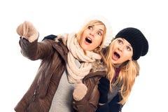 Femmes choqués au pointage de vêtements de l'hiver Photographie stock
