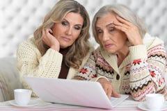 Femmes concentrées avec l'ordinateur portable Image libre de droits