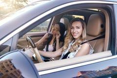 Femmes conduisant la voiture et regardant la caméra image libre de droits