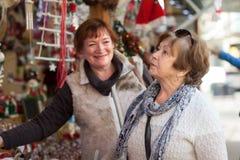 Femmes considérant des décorations au compteur du marché de Noël Photos stock