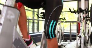 Femmes convenables établissant sur le vélo d'exercice banque de vidéos