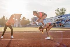 Femmes convenables dans le stade jouant la grenouille de saut Photos stock
