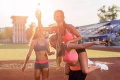 Femmes convenables de groupe donnant sur le dos à tour de jeunes amis heureux appréciant un jour au stade Photos stock